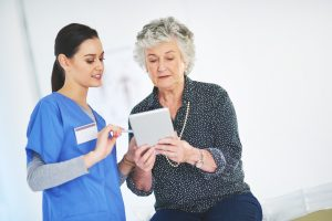 Shot of a kind young nurse looking at a tablet with her elderly patient in a healthcare center